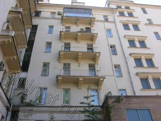 Альпинист грунтует поверхность балконных плит перед покраско.