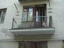 На данном фото показана часть  фасада после проведения ремонтных работ, видно, что поверхность фасада окрашена, а балконные плиты восстановлены.