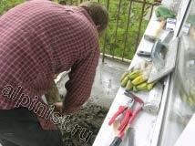 Мы подготовили плиту балкона к устройству стяжки, померили уровнем ширину доски для опалубки, установили ее и сейчас наш специалист занимается заливкой стяжки