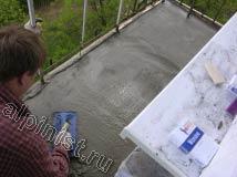 На большей части балконной плиты наш специалист провел устройство новой стяжки, сейчас он разглаживает ее теркой