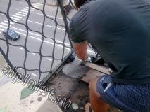 Наш специалист начал проводить демонтаж керамической плитки с пола балкона, на фотографии видно как он убирает плитки с пола.