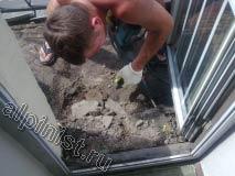 Сначала мы демонтировали керамическую плитку, теперь наш специалист с помощью отбойника отбивает старую стяжку с пола балкона.