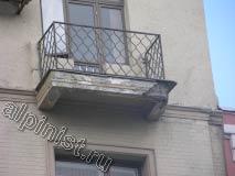 Угол балконной плиты одного из балконов сильно разрушен, уже видна торчащая арматура, штукатурка бухтит, и по ней идут глубокие трещины.
