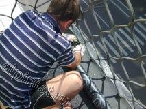 Сейчас наш специалист прорезает небольшие отверстия на кровельном рулонном материале, для того чтобы можно было обойти металлические ограждения балкона и покрыть стяжку полностью.