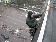 На данной фотографии, показан наш промышленный альпинист, который готовится спуститься на веревке вниз для выполнения демонтажа баннера