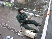 Наш специалист закрепил веревки на крыше, после чего, применяя технику промышленного альпинизма он спустится вниз к месту крепления банера для его последующего демонтажа