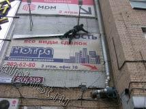Применяя технику промышленного альпинизма, наш специалист начал демонтаж рекламного банера с верхней части