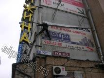 Для того, чтобы  снять репшнур с левой вертикальной стороны баннера, наш альпинист маятником раскачался на веревке и зацепился ногой за угол здания
