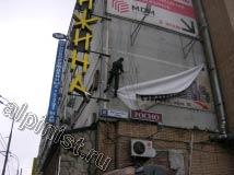 Наш промальпинист раскачался маятником на веревке и зацепился ногой за угол здания, после этого он пристегнулся карабином к металлоконструкции и спокойно снял репшнур, который крепил банер с левой вертикальной стороны