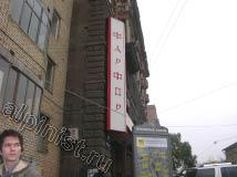 На предоставленной фотографии, виден рекламный панель-кронштейн, закрепленный вертикально к стене анкерами на высоте примерно уровня 3 - го этажа