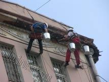 Наши альпинисты крепят металлическую сетку, сложенную в несколько слоев, перед оштукатуриванием карниза здания.