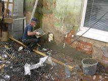 После того, как монтажная пена просохла, специалист нашей компании начал набрасывать и разглаживать  штукатурный раствор, предварительно полив поверхность стены водой.