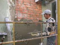 Мастер штукатур на поверхность кирпичной кладки накидывает штукатурный раствор и разглаживает его специальной теркой, для того чтобы слой раствора сровнять с поверхностью стены.