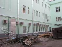 Фасадные работы на первом этаже здания завершены. На фотографии видно, что поверхность фасада первого этажа отремонтирована и покрашена,  а цоколь покрашен первым слоем.