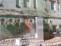 На этой фотографии видны металлические кронштейны под вторым этажом, которые держали провода. Наши специалисты срезали их болгаркой, т.к. они выступали из фасада, после чего покрыли их антикором и оштукатурили.
