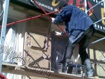 В данный момент мастер отбивает молотком бухтящую штукатурку в части фасада между окнами, где были большие разрушения.