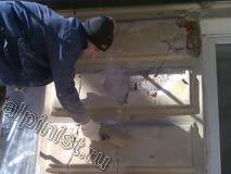 Сейчас, с помощью жесткой щетки, штукатур очищает предварительно расшитые трещины и сколы на фасаде от остатков отходящей штукатурки, пыли и грязи.