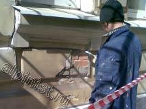 Штукатур расшивает трещины и сколы различными способами; болгаркой, молотком или как видно сейчас с помощью шпателя.