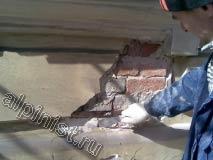 Штукатурка на фасаде здания в некоторых местах легко отходит, просто с помощью жесткого шпателя, что видно на фотографии.