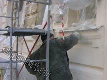 Сейчас наш штукатур зашкуривает зашпаклеванную поверхность фасада, шкуркой для сглаживания поверхности фасада.