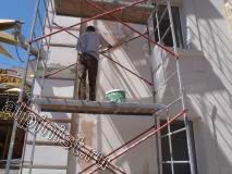 Наш специалист в данный момент проводит фасадные работы, а именно крепит стекловолокнистую сетку «Строби» на поверхность фасада и шпаклюет по ней фасадной шпаклевкой, откосы и архитектурные элементы мы также шпатлюем по сетке.