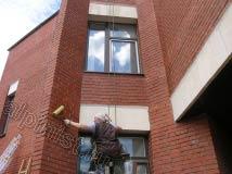 Очищенную от высолов часть фасада наш альпинист покрывает гидрофобизатором