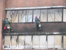 На данной фотографии показаны наши альпинисты, которые моют окна балкона и  очищают кирпичное здание специальным средством для очисти фасада после пожаров.