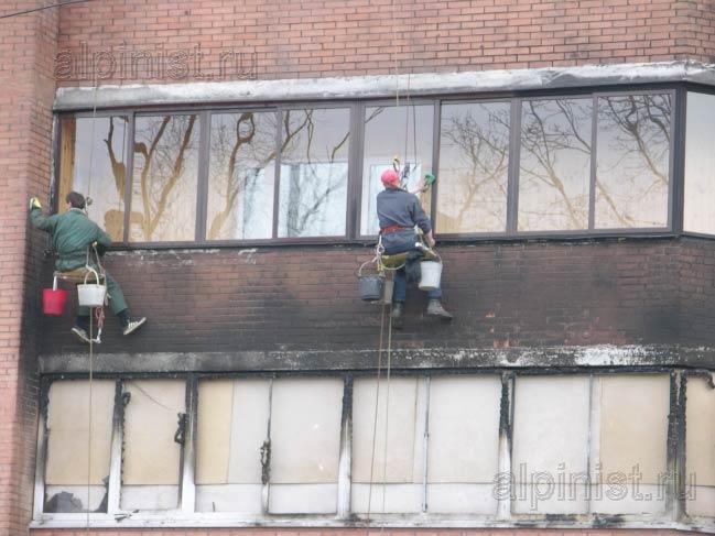 альпинисты моют окна балкона и очищают кирпичный фасад здания средством для очисти фасада от копоти