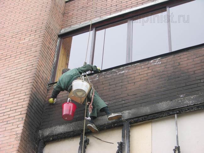 альпинист смывает копоть пожара, с фасада жилого кирпичного дома