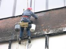 На этой фотографии наш промышленный альпинист наносит на фасад специальный раствор для очистки нагара после пожара, который расщепляет копоть и позволяет максимально счистить остатки гари.