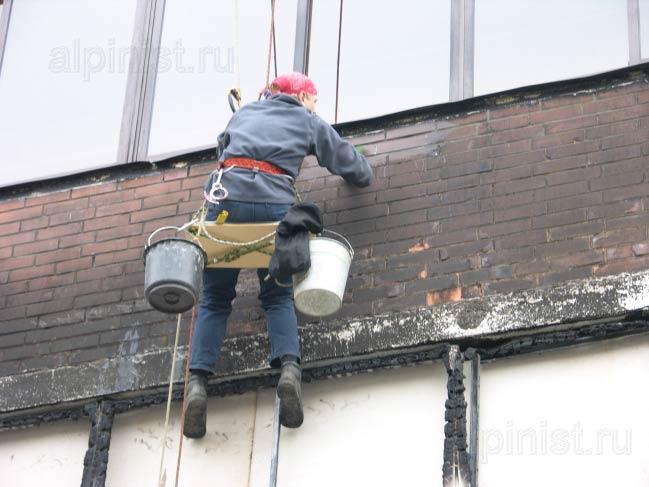 промышленный альпинист наносит на фасад специальный раствор для очистки нагара после пожара