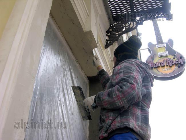 штукатур шпатлюет откосы фасадной шпатлевкой, предварительно откосы были оштукатурены