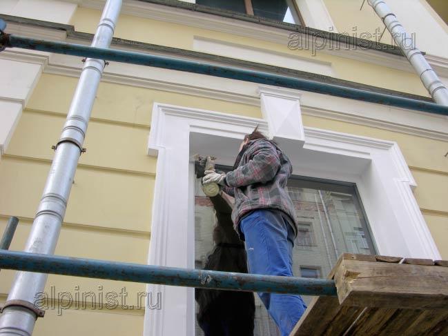 маляр заканчивает ремонтные работы по восстановлению оконных откосов