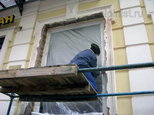 специалист закрывает окно пленкой, побрезав монтажную пену по периметру окна