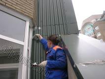 На этой фотографии показано, как наш специалист промазывает специальным герметиком примыкания металлического листа к стене