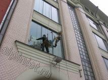 На фото видно, что наши промышленные альпинисты заканчивают мойку окон на первом оконном пролете,  в данной части фасада под окнами второго этажа установлены широкие козырьки, и наши альпинисты нижние окна моют стоя