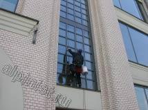 На этом фото показан наш альпинист, который, используя специальное снаряжение и технику промышленного альпинизма, моет оконный пролет с небольшими окнами с фасадной стороны
