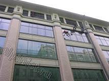 На данной части здания работают две бригады промышленных альпинистов, справа уже вымыли верхнее окно и начали спуск вниз, из другой бригады спустился пока один альпинист и начал мойку окон