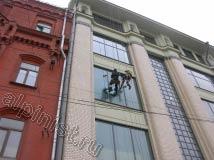 Наши альпинисты сейчас проводят мойку окон со стороны фасада здания, один специалист моет окно шубкой, а его напарник затирает специальной салфеткой примыкания стекла к профилю