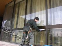 На данном фото показан наш специалист, который в настоящий момент промывает водой с помощью шубки нижнюю часть витража с наружной фасадной стороны.
