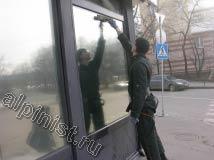 На данном фото показан наш специалист, который начал промывать шубкой с водой  витражное окно, в данной части фасада окна с зеркальным эффектом.
