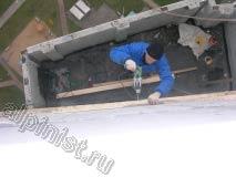 Для выполнения высотных работ по устройству крыши над балконом, наш специалист применяет дрель, которой сейчас высверливает отверстия для саморезов, которые крепят обрешетку кровли