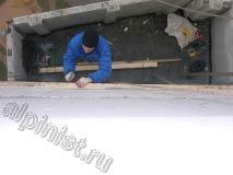 Предварительно просверлив отверстия в доске для обрешетки крыши и стене, наш мастер стал крепить доску анкерами и саморезами