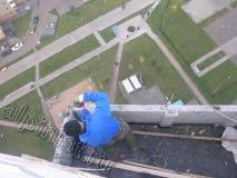 На фотографии видно, как наш мастер сейчас сверлит перфоратором отверстия на верхней части внешней стороны ложного балкона для крепления обрешетки кровли