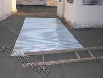 Форма балкона, над которым мы проводим устройство кровли, имеет трапециевидную форму, поэтому, нам нужно правильно отмерить и отрезать болгаркой нужные размеры оцинкованного профилированного металлического листа