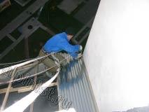 Применяя технику промышленного альпинизма наш специалист спустился на веревке вниз к обрешетке кровли, сейчас мы крепим первый лист профлиста кровли на обрешетку