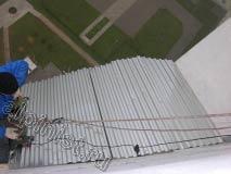 Листы металлического оцинкованного профилированного листа, мы  разрезали болгаркой по предварительно снятым замерам и сделанному раскрою, теперь наш специалист крепит эти листы к обрешетке крыши с помощью кровельных саморезов