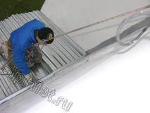 Применяя технику промышленного альпинизма, наш специалист спустился вниз на установленную крышу балкона и сейчас герметизирует примыкания между листами профнастила кровли и примыкания к стене