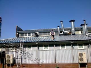 На фотографии видно нашего мастера, который в данное время проводит работы по покраске поверхности крыши.
