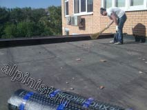 На предоставленной фотографии показан наш кровельщик, который в настоящее время готовит поверхность крыши к ремонту, а именно подметает мусор очищая поверхность.|